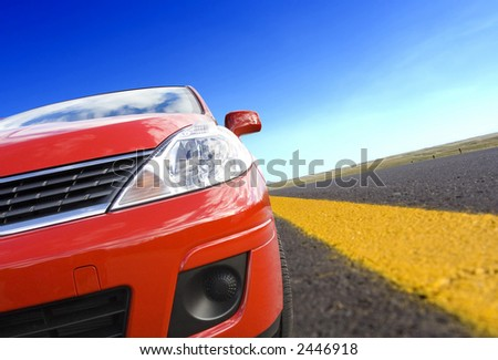 Red car on a  road with yellow line(tilted) - stock photo