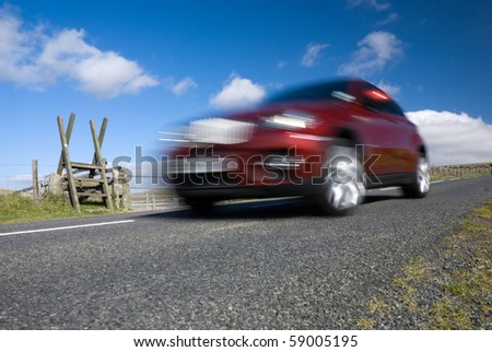 Red car speeding on empty mountain road. Dartmoor National Park, Devon, UK. - stock photo