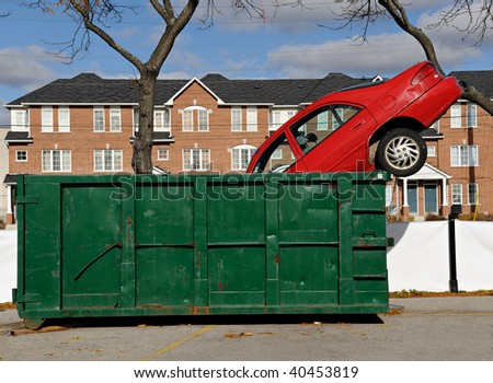 Red car thrown in a green dumpster - stock photo