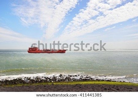 Red cargo ship (tanker) is sailing near Vlissingen, the Netherlands - stock photo