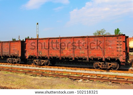 Red cargo wagons on railway over the blue sky - stock photo