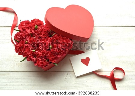 Red carnation heart shaped box with message card.Image of Mothers day - stock photo