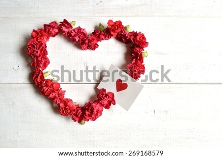 Red carnations heart shaped wreath with message card - stock photo