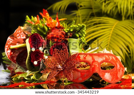 Red carnival masquerade mask with new year bouquet lying on palm tree background.Phuket, Thailand - stock photo
