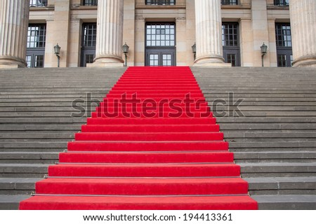 Red carpet on a steps principal staircase. - stock photo