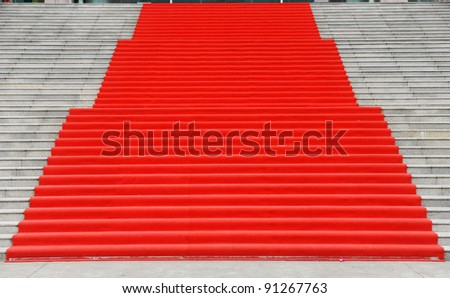 Red carpet on marble stairway welcoming VIPs. - stock photo