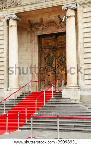 Red carpet over staircase for government officials or celebrities leading to beautiful historical stone building in Europe, hotel de ville, Lyon, France. - stock photo