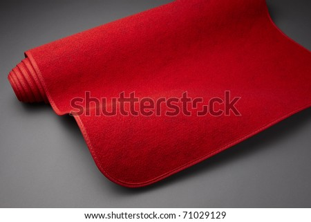 Red carpet starts to unroll - stock photo