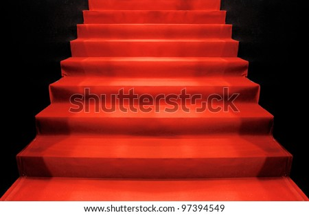 red carpet up stairs in the dark - stock photo