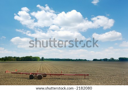 Red cart left on freshly harrowed field under summer sky with white clouds, green trees in the background - stock photo