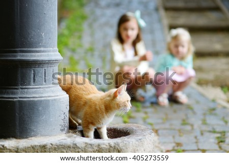 Red cat drinking out of city fountain in Italy with two kids watching in a background - stock photo