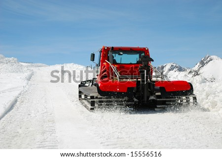 Red caterpillar tractor makes snow slope against blue sky on Pyrenees pass
