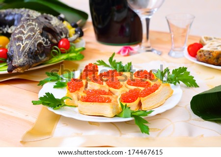 Red caviar and stuffed sturgeon baked on a platter with vegetables and greens