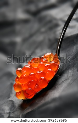 Red caviar in a metal spoon on a gray background vertical - stock photo