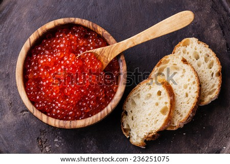 Red caviar in olive wood bowl and pieces of bread on dark background - stock photo