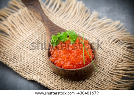 Red caviar in the wooden spoon. - stock photo