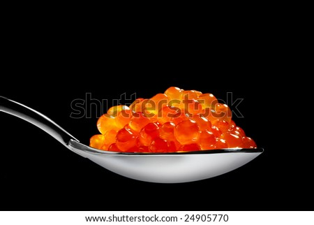 Red caviar isolated on black background - stock photo