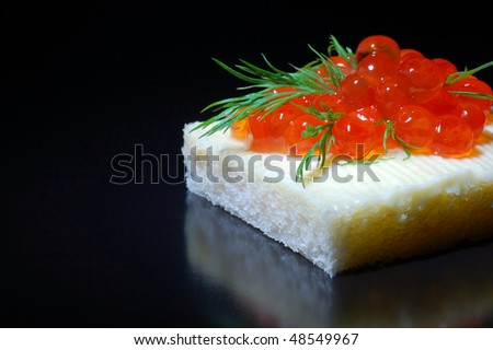 Red caviar on a piece of bread with butter and dill - stock photo