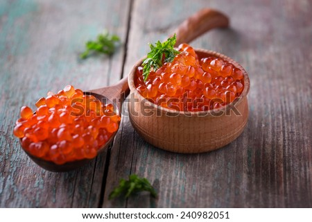 Red caviar  on aged wooden background. Selective focus is in caviar in bowl. - stock photo