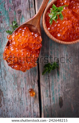 Red caviar  on aged wooden background. Selective focus is in caviar in spoon. - stock photo