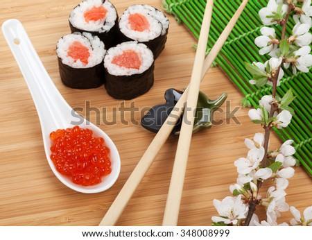 Red caviar, sushi set, sakura branch and chopsticks over bamboo table - stock photo