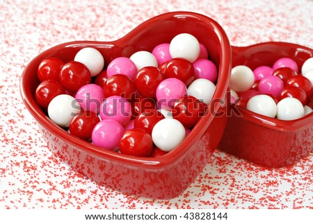 Red ceramic heart-shaped dishes with colorful valentine gumballs and red sugar sprinkled around.  Macro with shallow dof. - stock photo