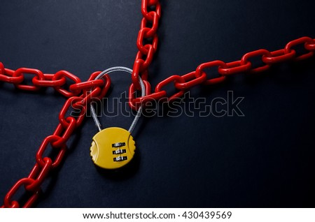 Red chain and yellow padlock with number combination on blackboard. - stock photo