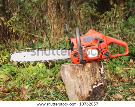 red chainsaw and wood .