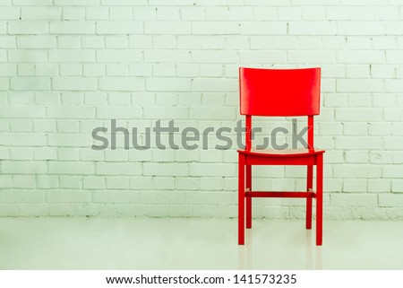 Red chair in empty room against a brick wall with copy-space - stock photo