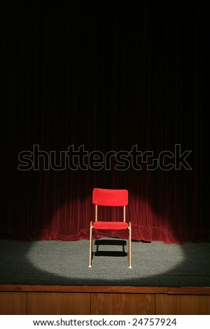 red chair on theatre stage lighted with spotlight, red curtain in background