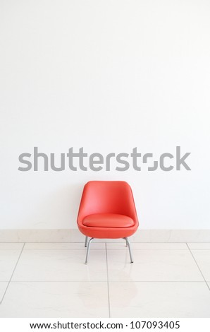 Red Chair to face a blank wall - stock photo