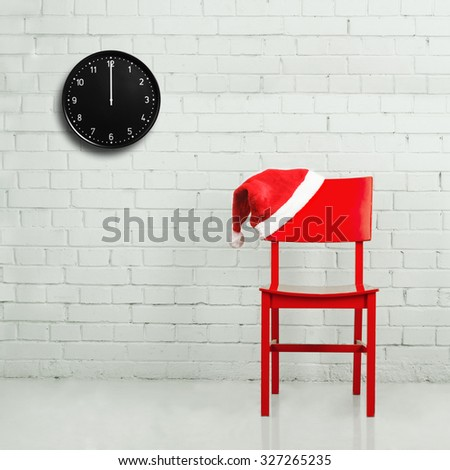 Red chair with Santa hat against white brick wall with clock showing twelve o'clock. Christmas time concept - stock photo