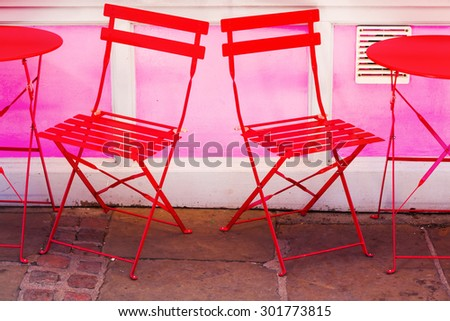 red chairs and table at a street cafe - stock photo