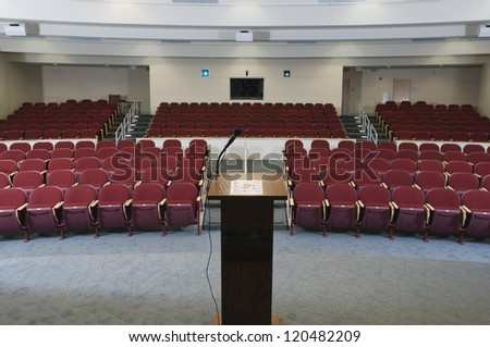 Red chairs arranged in order and podium at an empty conference room - stock photo