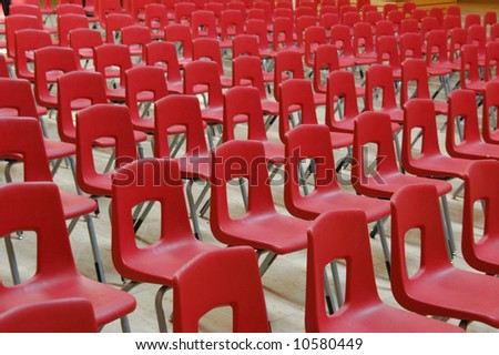 Red chairs arranged in rows for presentation