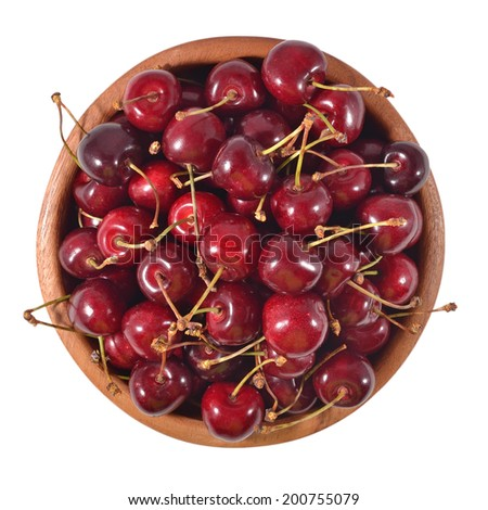 Red cherries in a wooden bowl on a white background