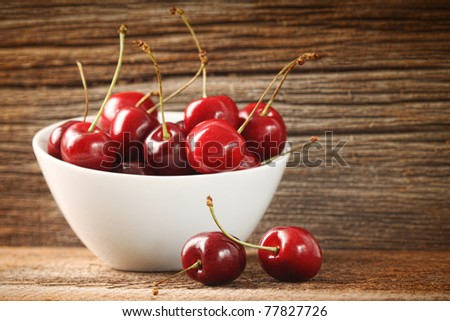 Red cherries in bowl on old barn wood - stock photo