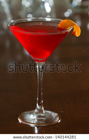 red cherry colored drink served up in a martini glass on a out of focus bar top - stock photo