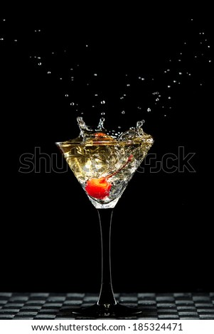red cherry falling in to a glass with liquor - stock photo