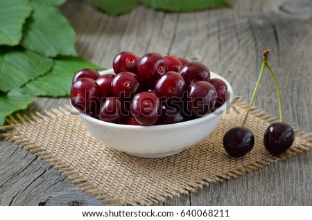 Red cherry in white bowl on wooden table