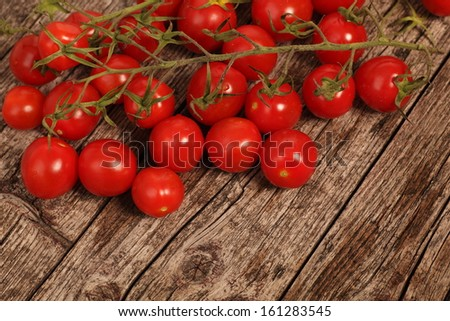 Red cherry tomatoes lying on a textured rustic wooden