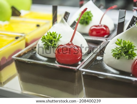 red cherry topped on chocolate cup cake  with green leaf . - stock photo
