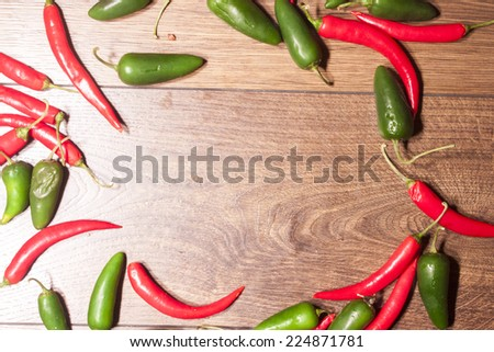 Red chili and green jalapeno, on wooden background - stock photo