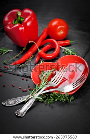 Red chili and paprika on the red heart shape plate - stock photo
