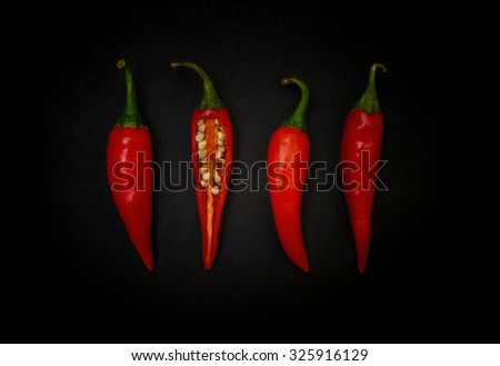 Red chili pepper on black background - stock photo