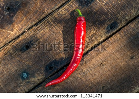 Red Chili Pepper Perfectly fresh Red Chili Peppers on the wooden table, lonely and hot! - stock photo