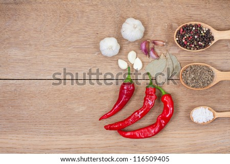 Red chili peppers, garlic, bay leaf, spices in spoons on wood texture background - stock photo