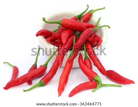 Red chili peppers in a ceramic bowl over white background