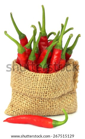 Red chili peppers in a sack bag over white background - stock photo