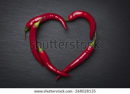 Red chili peppers in heart shape, indicating hot love for valentine's day, isolated on dark grey slate stone. - stock photo